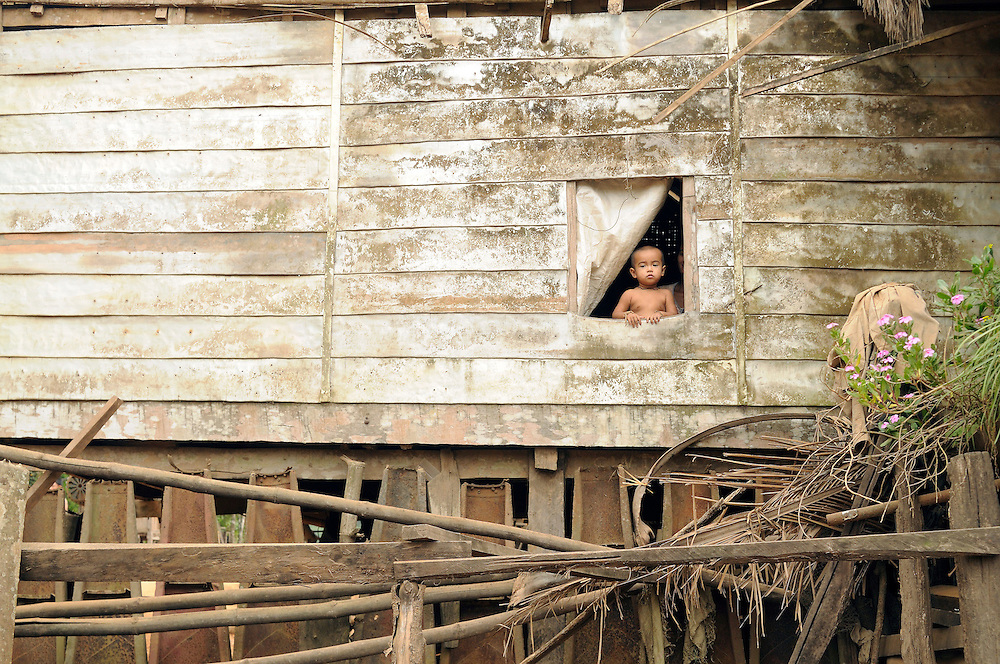 "In a village on the Ho Chi Minh Trail a young child looks out the window of his home constructed entirely from American cluster bomb casings.  The US Military dropped approximately 2 million tons of bombs on Laos making it, per capita, the most heavily bombed country in the world...Laos was part of a ""Secret War"", waged within its borders primarily by the USA and North Vietnam.  Many left over weapons supplied by China and Russia continue to kill.  However, between 90 and 270 million fist size cluster bombs were dropped on Laos by the USA, with a failure rate up to 30%.  Millions of live cluster bombs still contaminate large areas of Laos causing death and injury.  The US Military dropped approximately 2 million tons of bombs on Laos making it, per capita, the most heavily bombed country in the world. ..The women of Mines Advisory Group (MAG) work everyday under dangerous conditions removing unexploded ordinance (UXO) from fields and villages...***All photographs of MAG's work must include (either on the photo or right next to it) the credit as follows:  Mine clearance by MAG (Reg. charity)***."