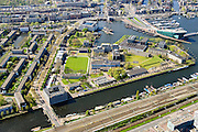 Nederland, Noord-Holland, Amsterdam, 09-04-2014;<br /> Marineterrein en Kattenburg (links), bovenin Scheepvaartmuseum en Prins Hendrikkade, de IJtunnel en museum Nemo met historische woonboten. <br /> Beneden de Dijksgracht en het spoor.<br /> Navy area and the National Maritime Museum (white building), right Museum Nemo.<br /> luchtfoto (toeslag op standard tarieven);<br /> aerial photo (additional fee required);<br /> copyright foto/photo Siebe Swart