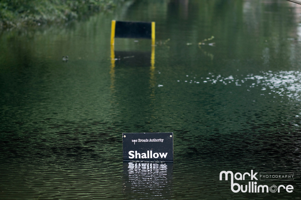 A sign in the water hald covered with Shallow just showing