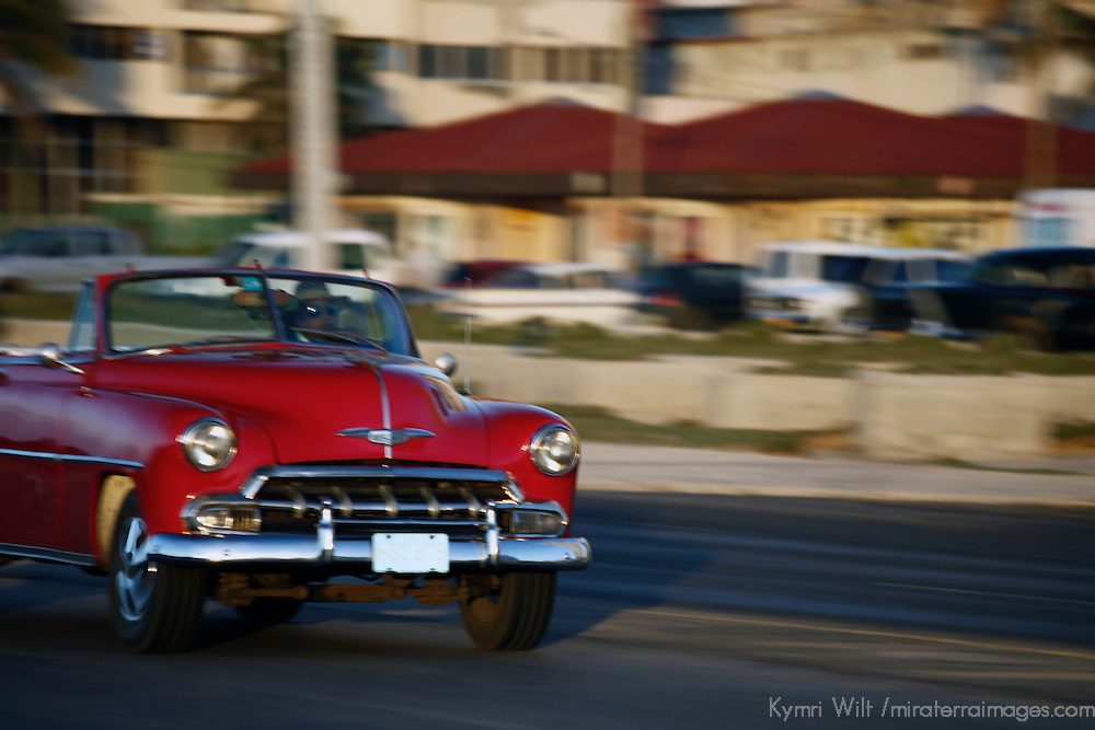 Central America, Cuba, Havana. Classic convertible car driving along the Malecon in Havana.