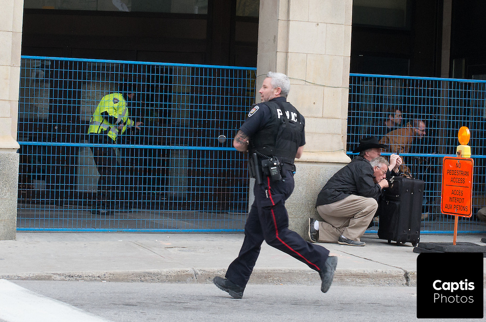 People take cover as police run towards the Rideau Centre shopping mall. The mall was placed under lock down following the shooting of Cpl. Nathan Cirillo minutes away at the National War Memorial. October 22, 2014.
