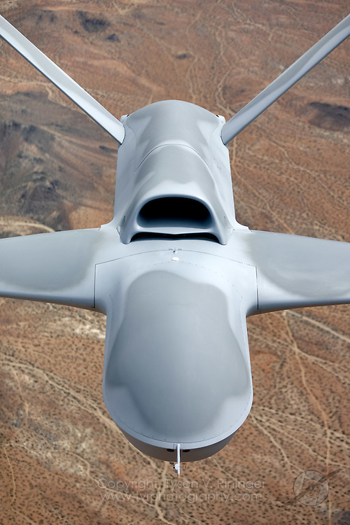 "An aerial view of General Atomics P46 Predator 'C', ""Avenger"" over the high deserts of Southern California. The latest generation Predator is a jet-powered remotely-piloted vehicle (RPV) that is nearly twice the size of its predecessor. Featuring an internal weapons bay, retractable gear, a blended wing design, top-mounted intake and shielded exhaust, the stealthy airframe can cruise at 50,000 feet and can perform multiple tasks from reconnaisance to attack roles."