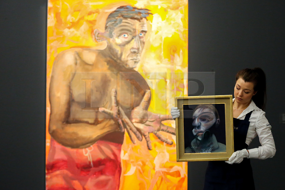 """© Licensed to London News Pictures. 21/06/2019. London, UK. A technician holds Francis Bacon's """"Self-Portrait"""", 1975 (Est £15m- £20m) in front of Albert Oehlen's Selbstportrait Mit Leeren Handen (Self-Portrait with empathy hands) 1988 (Est £4m- £6m) at the preview of Summer Contemporary Art Auctions at Sotheby's George Street, London. Photo credit: Dinendra Haria/LNP"""