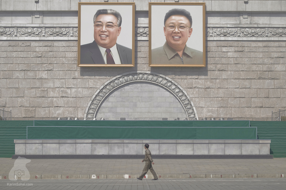 "A man walks under giant portraits of the ""Eternal Leader"" and the ""Dear Leader"", on Pyongyang's Kim-Il Sung Square, a place of great cultural significance, as it is a common gathering place for rallies, dances and military parades. Both Kims are now dead and the DPRKs current ruler is the third in the dynasty, Kim Jong-un, the son of Kim Jong-il and the grandson of Kim Il-Sung. In April 2012, Kim Jong-un was formally given the title of Supreme Leader. He is not even 30 years old."