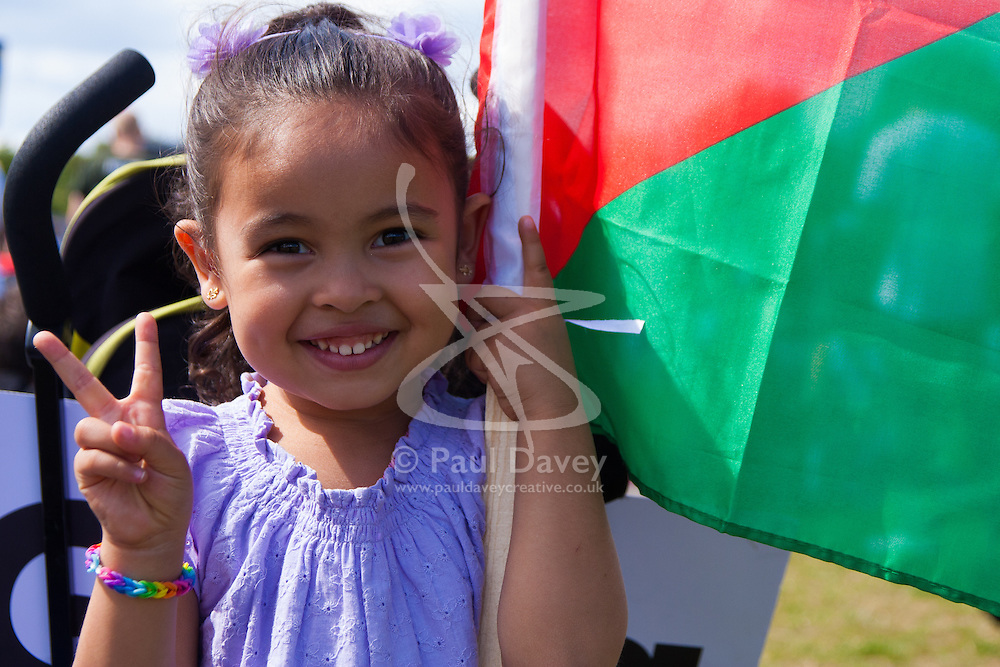 London, August 9th 2014. A little girl gives a 'V' for victory sign as she and her parents along with up to 150,000 others, attend the post-march rally in Hyde Park.