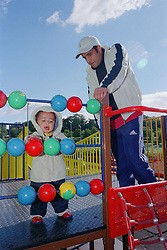 Father watching young son playing with toys on climbing frame in playground,