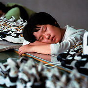 Athletic shoe factory workers naps during their break time in Guangzhou, China.