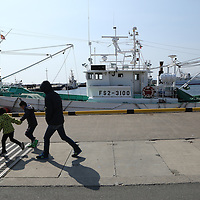 February,28.2016 Onahama,main port of Fukushima prefecture ,pMan and  children walk on Onahama harbour, behind them a small  fishing boat from Fukushima prefecture which are allow to go fishing ecxept one time per a week to collect sample of fish. since  Nuclear accident at Fukushima prefecture , hugh levels of radioactive material were discovered in seafoods. Pierre Boutier