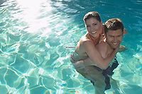 Man giving woman piggy back in swimming pool, portrait