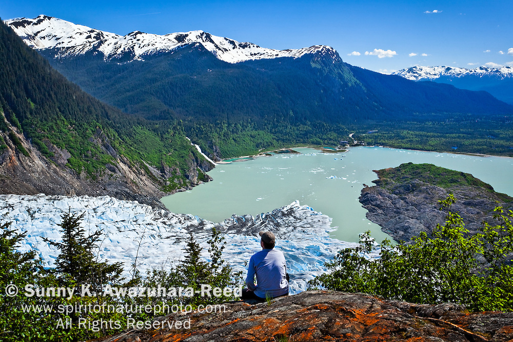 A male hiker looking down  Mendenhall Glacier and Mendenhall Lake from West Glacier Trail, Juneau, SE Alaska, on a sunny day, early summer. Model Released #0092010MR