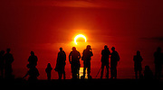 Viewers at Dog Beach in San Diego, California, USA, watch an annular solar eclipse in progress.