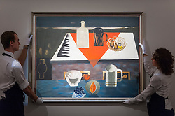 "© Licensed to London News Pictures. 18/11/2016. London, UK. Technicians prepare to hang ""The Red Cloth"" by Mary Fedden (est. GBP15-20k), at the preview at Sotheby's of works on view at four upcoming November auctions featuring Modern & Post-War British Art, A Painter's Paradise (Julian Trevelyan & Mary Fedden at Durham Wharf), Scottish Art and Picasso Ceramics from the Lord & Lady Attenborough Private Collection. Photo credit : Stephen Chung/LNP"