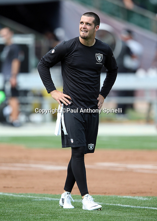 Oakland Raiders quarterback Derek Carr (4) looks on while warming up before the 2015 NFL week 1 regular season football game against the Cincinnati Bengals on Sunday, Sept. 13, 2015 in Oakland, Calif. The Bengals won the game 33-13. (©Paul Anthony Spinelli)