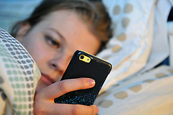 A teenage girl uses her phone in bed to chat to friends UK MR