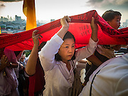 18 NOVEMBER 2015 - BANGKOK, THAILAND: People a red cloth inscribed with prayers up to the chedi at Wat Saket during the parade marking the start of the temple's annual fair. Wat Saket is on a man-made hill in the historic section of Bangkok. The temple has golden spire that is 260 feet high which was the highest point in Bangkok for more than 100 years. The temple construction began in the 1800s in the reign of King Rama III and was completed in the reign of King Rama IV. The annual temple fair is held on the 12th lunar month, for nine days around the November full moon. During the fair a red cloth (reminiscent of a monk's robe) is placed around the Golden Mount while the temple grounds hosts Thai traditional theatre, food stalls and traditional shows.      PHOTO BY JACK KURTZ