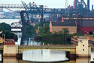 Seen from high above on the abandoned Cline Avenue structure, the Indiana Harbor Canal is lined with bridges and industry. In the foreground is the Dickey Road drawbridge, further back is the Norfolk Southern drawbridge at CP Hick, and the ArcelorMittal Indiana Harbor Steel Mill Works looms over the scene.