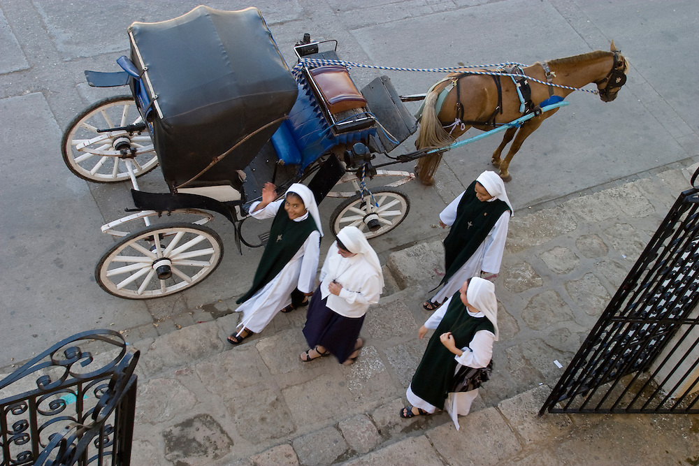 Mexico, Yucatan, Izamal, nuns walking by horse-drawn carriage (viewed from above)