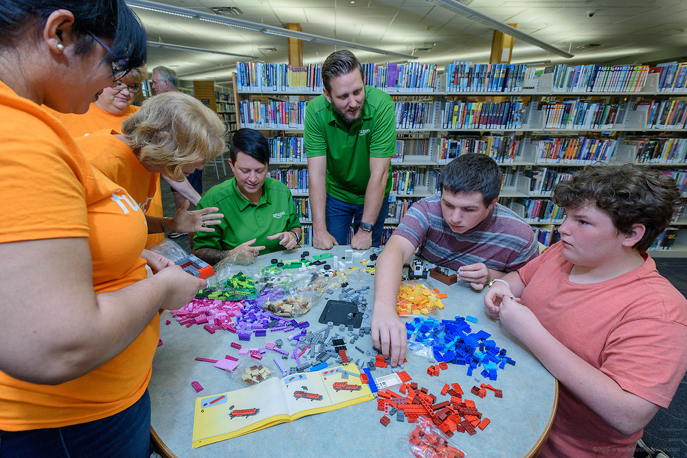 Amazon associates and leaders Ashley Hutchins and Brett Gorin share a table covered in Lego pieces with students Justin Johnston, 15, and Isaac Stepp, 14. Leaders from Amazon present a donation of $10,000 in new technology to support Bullitt County Library's STEM and STEAM programs for students in the Bullitt County School District Tuesday, July 10, 2018 at the Ridgway Memorial Library in Shepherdsville, Ky. The donation will enhance the library's current Digital Tech and Makerspace Lab programs and ignite more students to take advantage of STEM education outside of the classrooms and included Oculus Go headsets, a Cubelets classroom, and several sets of LEGOs that will increase the lab's ability to help students learn and explore STEM. (Photo by Brian Bohannon)