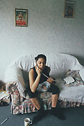 A woman holding her baby talking on the phone, UK, 2000's