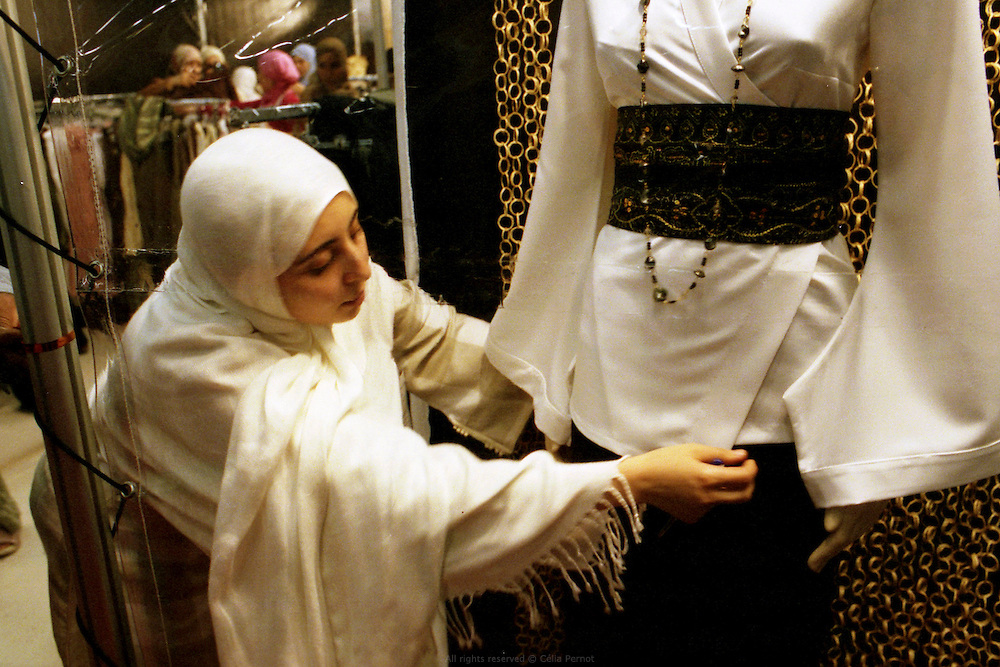 Karima Saouli pr&eacute;parant la vitrine de son stand &agrave; la rencontre annuelle des Musulmans de France au salon du Bourget, 2006. <br /> Karima Saouli, pioneer of muslim fashion design, arranging her booth at the French Muslims' annual meeting, Bourget fair, 2006.
