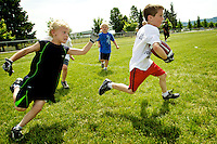 Colton Simkins, 6, slips past Aaden Anderson, 7, during a scrimmage game at the Idaho Vandal's football camp Tuesday.