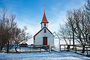 Quaint typical traditional church Braedratungukirkja with red roof in snowy landscape in Iceland