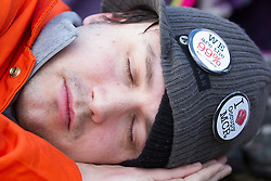 © Licensed to London News Pictures . 16/03/2013 . Manchester , UK . A man lies on the ground as if asleep as part of a protest against the Bedroom Tax . Hundreds of protesters opposed to changes to housing benefit , known as the Bedroom Tax , in Piccadilly Gardens in Manchester City Centre today (16th March) as part of a coordinated campaign of demonstrations in cities across the UK . The government plans to introduce changes to housing benefit from this April which will see some claimants receive a reduced amount if they have excess living space . Photo credit : Joel Goodman/LNP