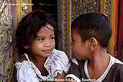 A young girl stares back at a boy at a temple in Phnom Penh, Cambodia.