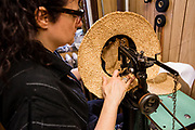 Sewing a headband into a straw hat on an old chain-stitch sewing machine with a high open arch and a short, narrow free arm.
