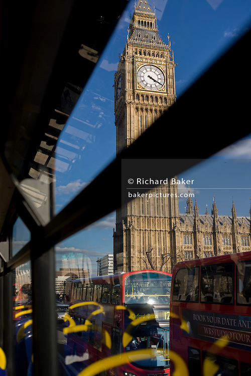 Parliament's Big Ben yellow seating handles from the top deck of a London double-decker bus.