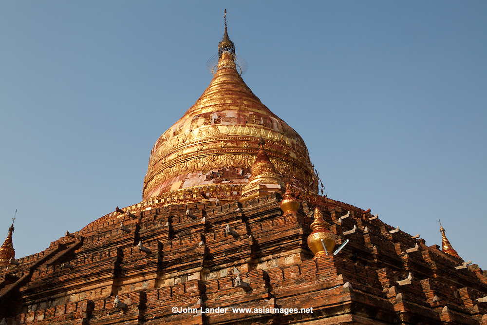 Dhamma Yazaki Paya is a pentagonal zedi with an unusual design.  Set in the south central plain of Bagan it has alovely views from its highest terrace.  Its gilded bell can be seen from miles around, and is one of the best though unused sunset viewing spots in Bagan because of its inconvenient location.