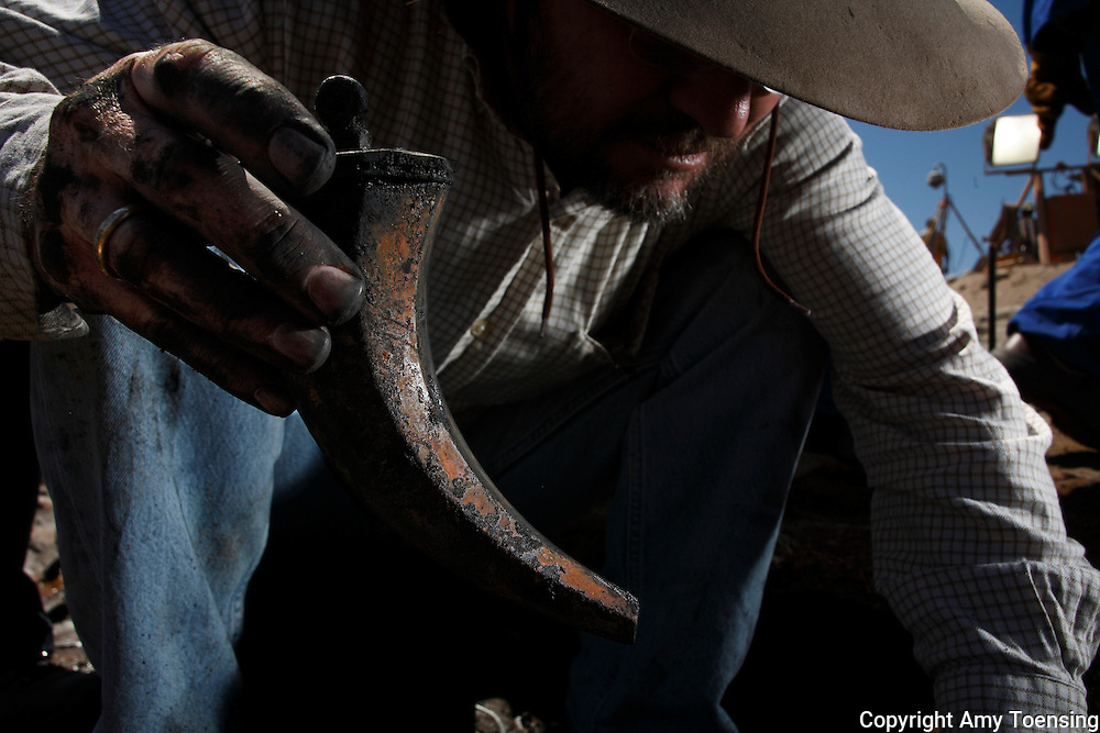 ORANJEMUND, NAMIBIA -- SEPTEMBER 29: Archeologist Dieter Noli holds an artifact on September 29, 2008 in Oranjemund, Namibia. The wreck was discovered by miners in the Namdeb diamond mine off the coast of Namibia. The ship was found seven meters below sea level on April 1, 2008. Archeologists presume the wreck is from the early 1500s. Most of the the artifacts found are being stored in a storage shed at the Namdeb Diamond Mine. Items include: copper ingots, bronze canons, canon balls, pewter bowls and plates, ivory tusks from African elephants, and most substantial over 2000 gold coins- approximately 21 kg - the most gold found in Africa since the Valley of the Kings in Egypt. (Photo by Amy Toensing) _________________________________<br />