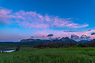 A photographer and participant at my June 17, 2018 Night Photography Workshop in Waterton Lakes National Park, at Maskinonge, in the evening twilight, with the clouds lit by the setting Sun.<br /> <br /> A single exposure with the Sigma 20mm lens and Nikon D750.