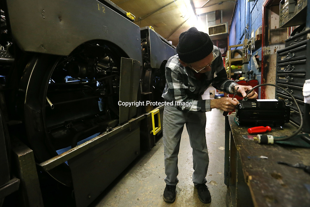 Morton works on wiring up a new motor for an excelerator. The motor drives a belt system that shoots the bowling ball back to the front for the bowler.