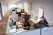 Monica Nezzer and Patrick Arite at their desks inside the Student Support Center where they work when not giving tours.  Nezzer and Arite are students at the University of New Mexico and are working 15-30 hours per week giving campus tours in order to help put themselves through college. (Steven St. John for NPR)