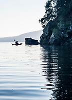 A sea kayaker glides over the glassy water as she rounds Second Sister Island with Salt Spring Island in the distance, BC, Canada.