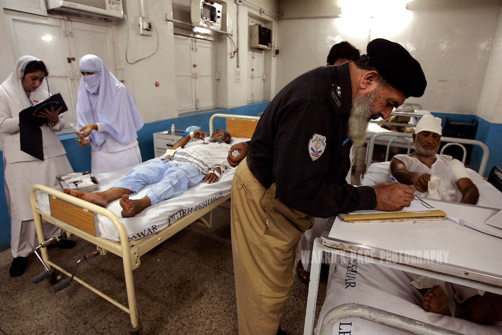 PESHAWAR, PAKISTAN - MAY 16: Police question survivors of the Marhaba Hotel bombing at the Lady Reading Hospital in Peshawar, May 16, 2007. Twenty five people were killed and dozens injured in an suicide bombing yesterday afternoon aimed at killing the owner of the hotel Marhaba and his alleged involvement with providing information to foreign intelligence agencies and as retaliation for the killing of Mullah Dadullah by NATO forces in neighbouring Afghanistan. (Photo by Warrick Page)