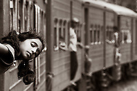 """A journey on the Sri Lankan Railway offers a whole new insight to the culture. Travelling at a maximum of 30 mph you can watch the world go by. The trains themselves are like giant toys with real people inside. As I was hanging out the window with my camera to my eye, this little girl appeared in my frame. Once she realised I was holding a camera, she retrieved her younger brother and moments later appeared smiling and waving from the carriage door."""