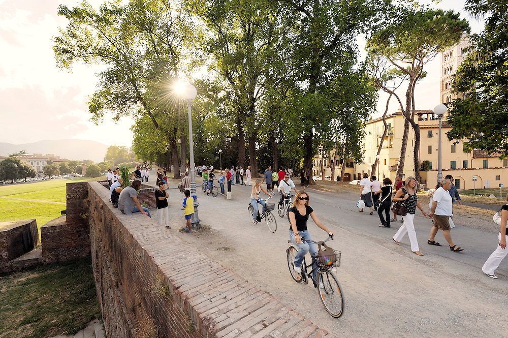 Italian city of Lucca. Local residents promenade and cycle along the mediaeval city walls each summer evening. Tuscany, Italy