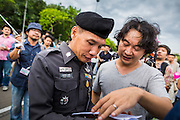 "24 JUNE 2014 - BANGKOK, THAILAND: A Thai police officer (left) talks to a poet (right) after he read it aloud at a meeting of the Monsoon Poets Society in Bangkok. Members of the ""Monsoon Poets Society"" gathered in front of the Anantasamakom Throne Hall Tuesday to pay homage to the People's Party, a Siamese (Thai) group of military and civil officers (which became a political party) that staged a bloodless coup against King Prajadhipok (Rama VII) and changed Thailand (then Siam) from an absolute monarchy to a constitutional monarchy on 24 June 1932. Since the coup against the civilian government on 22 May, the ruling junta has not allowed political gatherings. Although police read the poems, they did not arrest any of the poets or make any effort to break up the gathering.     PHOTO BY JACK KURTZ"