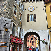 La Porte Sainte-Claire in Annecy, France <br /> La Porte Sainte-Claire once served as a gate through the walls of Medieval Annecy. The portal is named after a former convent for the poor. The arch leads through Passage Nemours. This is typical of the cobblestone alleys you will walk along while exploring the treasures of Old Town.