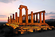 General view of the Temple of Juno or Hera Lacinia, c.450 BC, Agrigento, Sicily, Italy,  pictured on September 11, 2009, floodlit against a dramatic evening sky. This temple was built on an artificial spur. Standing on a high rectangular platform above four steps its 34 fluted columns consist of four tamburi or drums and are each 6.32 meters high. Today, 30 columns are standing but only sixteen with their capitals. After being damaged in the fire of 406 BC it was restored in Roman times, and again in 1787 by the Prince of Torremuzza. The Valley of the Temples is a UNESCO World Heritage Site. Picture by Manuel Cohen.