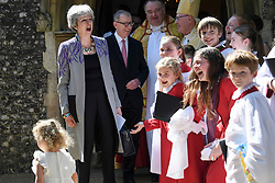© Licensed to London News Pictures. 21/04/2019. Maidenhead, UK. British Prime Minister THERESA MAY and her husband PHILIP MAY share a joke with young members of the church choir as they leave an Easter Sunday church service in the Prime Minster's constituency. Photo credit: Ben Cawthra/LNP