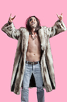 Young man in fur coat gesturing rock music sign over pink background