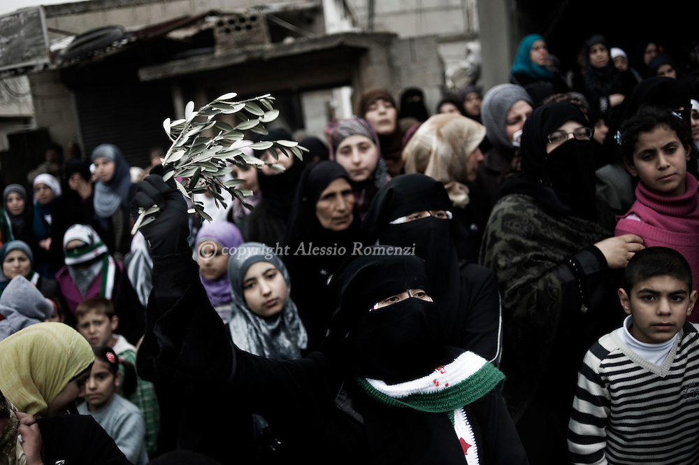 SYRIA - Al Qsair. Syrian woman waves an olive palm during the funeral of the the three men kidnapped and tortured by shabiha (militias of the regime) during three days. The bodies were found  in a main street of Al  Qsair, on February 14, 2012. ALESSIO ROMENZI