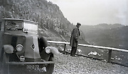man with a Renault tourer car taking in the mountain view 1920s