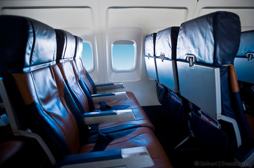 Row of three empty airline seats with a window showing a blue sky.