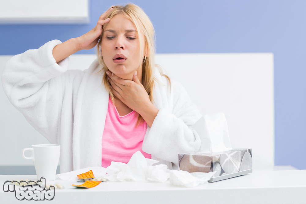 Young woman coughing while suffering from headache and cold in kitchen