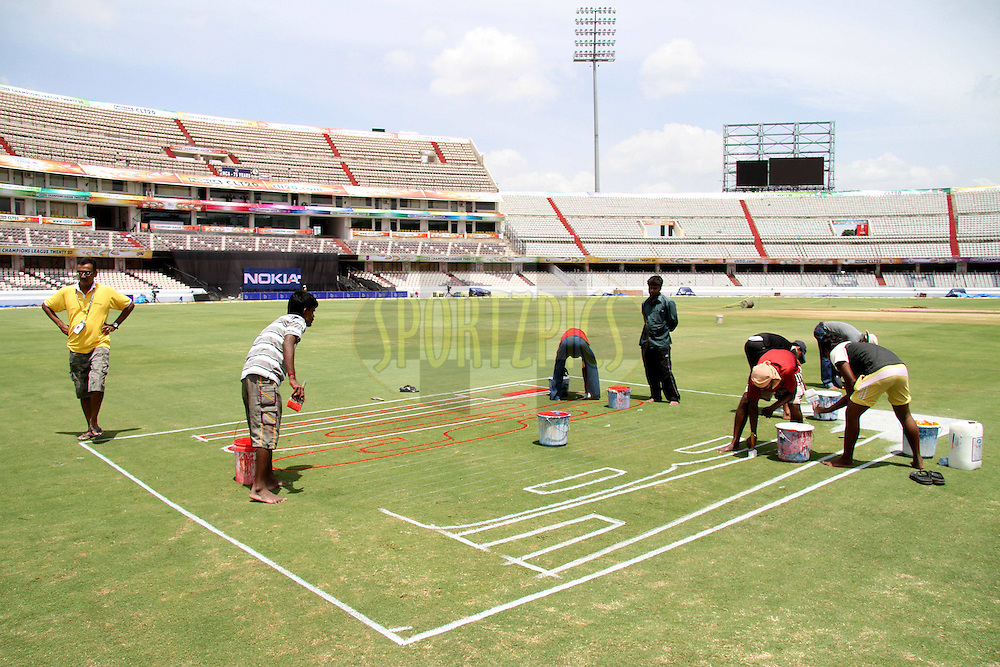 Groundstaff paint the sponsors logo onto the field during Ruhunu Eleven's training session held at the Rajiv Gandhi Cricket Stadium in Hyderabad, Andhra Pradesh, India on the 17 September 2011...Photo by Shaun Roy/BCCI/SPORTZPICS