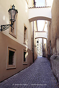 Lamp and archways over a cobbled pedestrian lane in the quiet streets of the Old Town beneath Prague Castle, Czech Republic